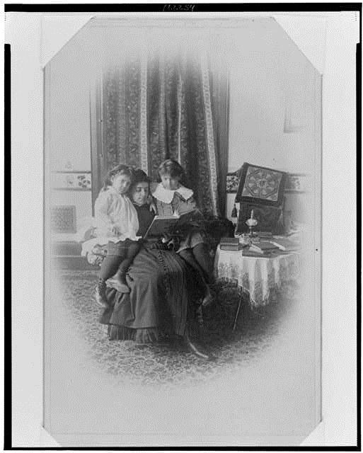 Marian Hubbard (1880–1962) und Elsie May Bell (1878-1964) mit Gouvernante, Schwarz-Weiß-Photographie, ca. 1885, unbekannter Photograph; Bildquelle: Library of Congress, Prints and Photographs Division Washington, Gilbert H. Grosvenor Collection of Photographs of the Alexander Graham Bell Family, Reproduction Number: LC-USZ62-122254, http://www.loc.gov/pictures/item/00649940/.