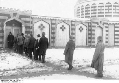 """Wünsdorf, Halbmondlager, sowjetische Flüchtlinge; Originalbildunterschrift: """"Im Lager der Mohamedanischen Rotgardisten! Bei den in den Kämpfen zwischen Sowjet Russland und Polen nach Ostpreußen übergetretenen bolschewistischen Divisionen befand sich auch eine grosse Anzahl Mohamedaner aus den Tartatenstämmen der Krim und des Kaukasus. Um diesen die Befriedigung ihres religiösen Bedürfnisses zu geben, hat die deutsche Regierung diese Internierten abgesondert und sie in dem sogenannten Halbmondlager in Wünsdorf bei Zossen (Nähe Berlin) untergebracht. In diesem Lager waren bereits während des Krieges mohamedanische Gefangene. Die Moschee des Lagers ist eine frühere Stiftung des ehemaligen deutschen Kaisers. Die jetzige deutsche Regierung hat es unternommen, diese mohamedanischen Rotgardisten, die zum Teil Analphabeten sind, durch passende Lehrer aus ihrer Mitte selbst zu unterrichten, um Ihnen über die Einförmigkeit der Internierung hinwegzuhelfen und hat ihnen eine Bibliothek von türkischen und russischen Werken sowie einen Lesesall zur Verfügung gestellt. Die Lagerküche bereitet den Internierten das Essen nach mohamedanischen Ritus und wird täglich durch den sogenannten Mulla (Moh. Oberpriester) geprüft. Der Anblick der Internierten die bunt zusammengewürfelt gekleidet sind, ist für den Besucher höchst originell.Auf dem Weg zur Moschee"""", Schwarz-Weiß-Photographie, 1920, Photograph: A. Frankl; Bildquelle: Deutsches Bundesarchiv (German Federal Archive), Bild-146-1995-051-37, Wikimedia Commons, http://commons.wikimedia.org/wiki/File:Bundesarchiv_Bild_146-1995-051-37,_W%C3%BCnsdorf,_Halbmondlager,_sowjetische_Fl%C3%BCchtlinge.jpg.Creative Commons Attribution-Share Alike 3.0 Germany."""