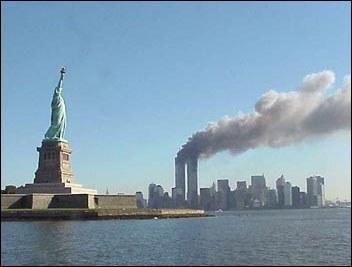 Skyline New Yorks am Morgen des Terroranschlags vom 11. Septembers 2001 mit den brennenden Zwillingstürmen des World Trade Centres; Bildquelle: National Park Service,  public domain; http://www.nps.gov/remembrance/statue/index