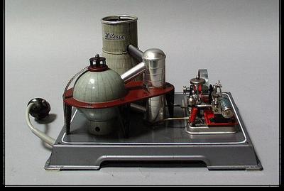 """Elektrische Dampfmaschine """"Atomkraftwerk R 200"""", Werkstatt: Wilhelm Schröder und Co., Lüdenscheid, Material/Technik: Weißblech, Metall / lithografiert, gebogen, genietet, Maße: 19 cm (Höhe), 31 cm (Breite), 24,5 cm (Tiefe), Bildquelle:"""