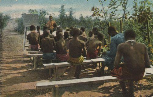 Missionsschule in Rubengera am Kiwusee, Ruanda, farbige Bildpostkarte, o. J. [um 1900], unbekannter Urheber, Verlag: Bethel-Mission Bielefeld; Bildquelle: Zenodot Verlagsgesellschaft mbH, Zeno.org, http://www.zeno.org/Bildpostkarten/M/Kolonien,+Mission/Afrika/Ruanda,+Missionsschule+in+Rubengera+am+Kiwusee.