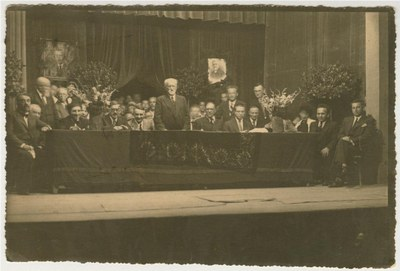 Simon Dubnow (standing, center) at the 1st international YIVO conference, Vilna, Poland. Other historians and notables on the stage and dais include (seated, from left) Joseph Tshernikhov, Elias Tcherikower, Yankev Botoshansky; (behind Botoshansky's left shoulder) Zelig Kalmanovitch; (to Dubnow's right) Ignacy Schiper; (behind Dubnow's right shoulder) Rafail Abramovich; (seated, first to fourth from right) Yudl Mark, Yankev Shatzky, Max Weinreich, Zalmen Reyzen; (standing behind Weinreich), Nakhman Meisel. The portrait of Tsemaḥ Szabad (right) is draped in black in commemoration of his death, which had occurred a few months earlier.