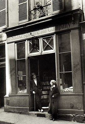 James Joyce and Sylvia Beach outside the door of Shakespeare and Company on the Rue de l'Odéon, black-and-white photograph, Paris 1920, unknown photographer; source: Poetry/Rare Books Collection, University Libraries, State University of New York at Buffalo, http://library.buffalo.edu/pl/.