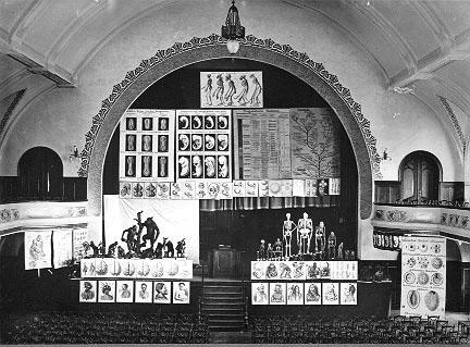 """Vortrag Ernst Haeckels (1834–1919) im """"Volkshaus"""" in Jena über die Abstammung des Menschen; Schwarz-Weiß-Photographie, unbekannter Photograph, 1907; Bildquelle: © Ernst-Haeckel-Haus, Jena, http://www.ehh.uni-jena.de/."""